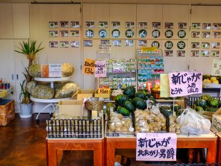 The rear wall of the market displays pictures and information of each farm