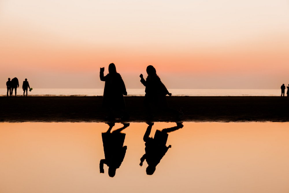 The setting sun turns these young girls into orange-hued silhouettes
