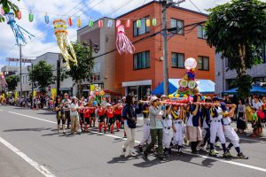 Children parade down the street carrying decorated dashi floats