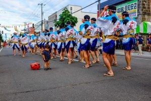 นักเต้นพื้นเมืองเดินขบวนไปบนถนน