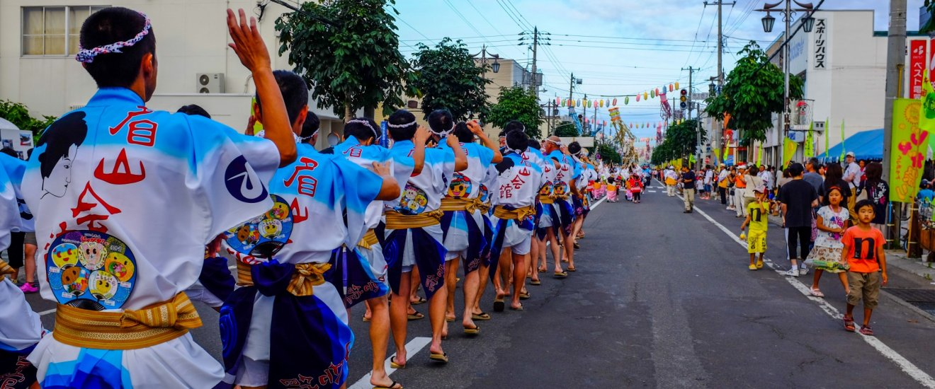 Enthusiastic dancers parade down the street in the afternoon dressed in colorful traditional dress