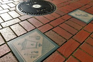 Designs of the gas lamp and horse carriage tiles along with a Yokohama manhole.