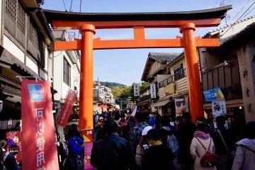 Busy street with torii in Kyoto leading to Fushimi Inari Taisha