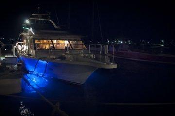 <p>เรือสำราญยามราตรีมีไฟแอลอีดีสีน้ำเงินฉายอยู่ใต้เรือ</p>