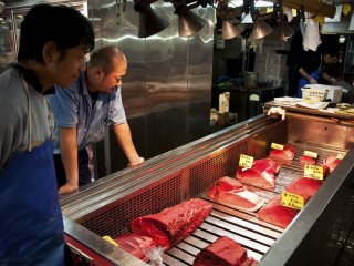 A couple of traders checking the quality of the tuna chunks