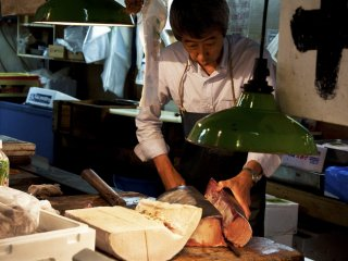 Trader cutting the tuna meat into small pieces
