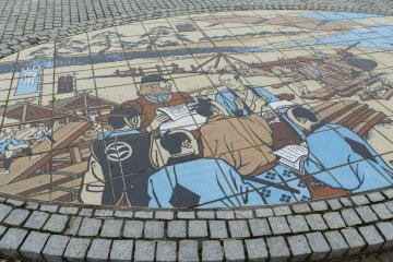 These tiles depict the building of Japan's first warship