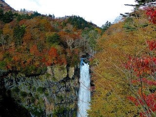 Blue sky and colorful leaves surround the falls