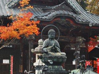 Patung Buddha yang sedang duduk di pelataran kuil.