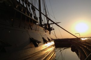 The ship's starboard cannons slumber silently in their hatches during the sunset.