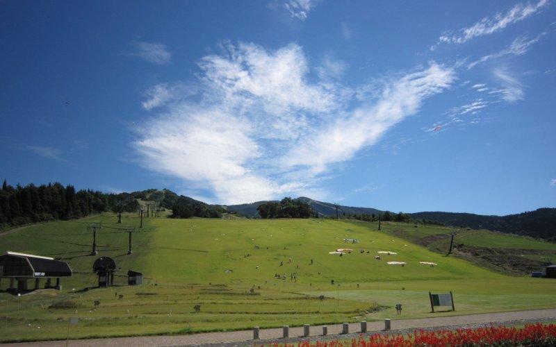 잔디의 스키장. 정어리 구름이 낀 가을 하늘에 패러글라이더가 반짝이고 있다