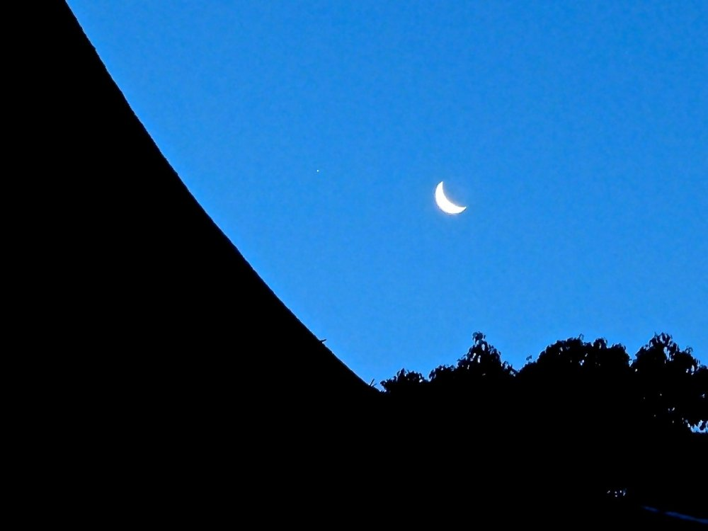 Crescent moon hanging over the shrine and forest