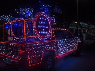 Vários veículos iluminados desfilam pelas ruas à noite