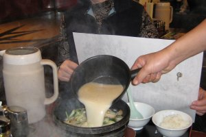 Steam, noise and bubbling result as the ramen is poured into the heated stone bowl by the server
