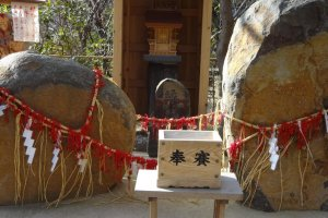 Two big stones tied to each other with fancy red string. These are the gods of matchmaking. If you throw coins into an offertory box and then pray to the gods seriously your desires will be answered!