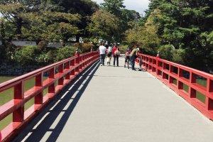 ทางเข้าเป็นสะพานแดง ข้ามบ่อน้ำ