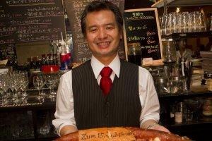 EZee Caféオープン15周年記念プレゼントを受け取る店のオーナー、中川浩一氏