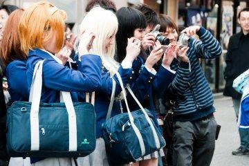 <p>K-On Cosplayers taking photos at Nipponbashi Street Festa 2010</p>