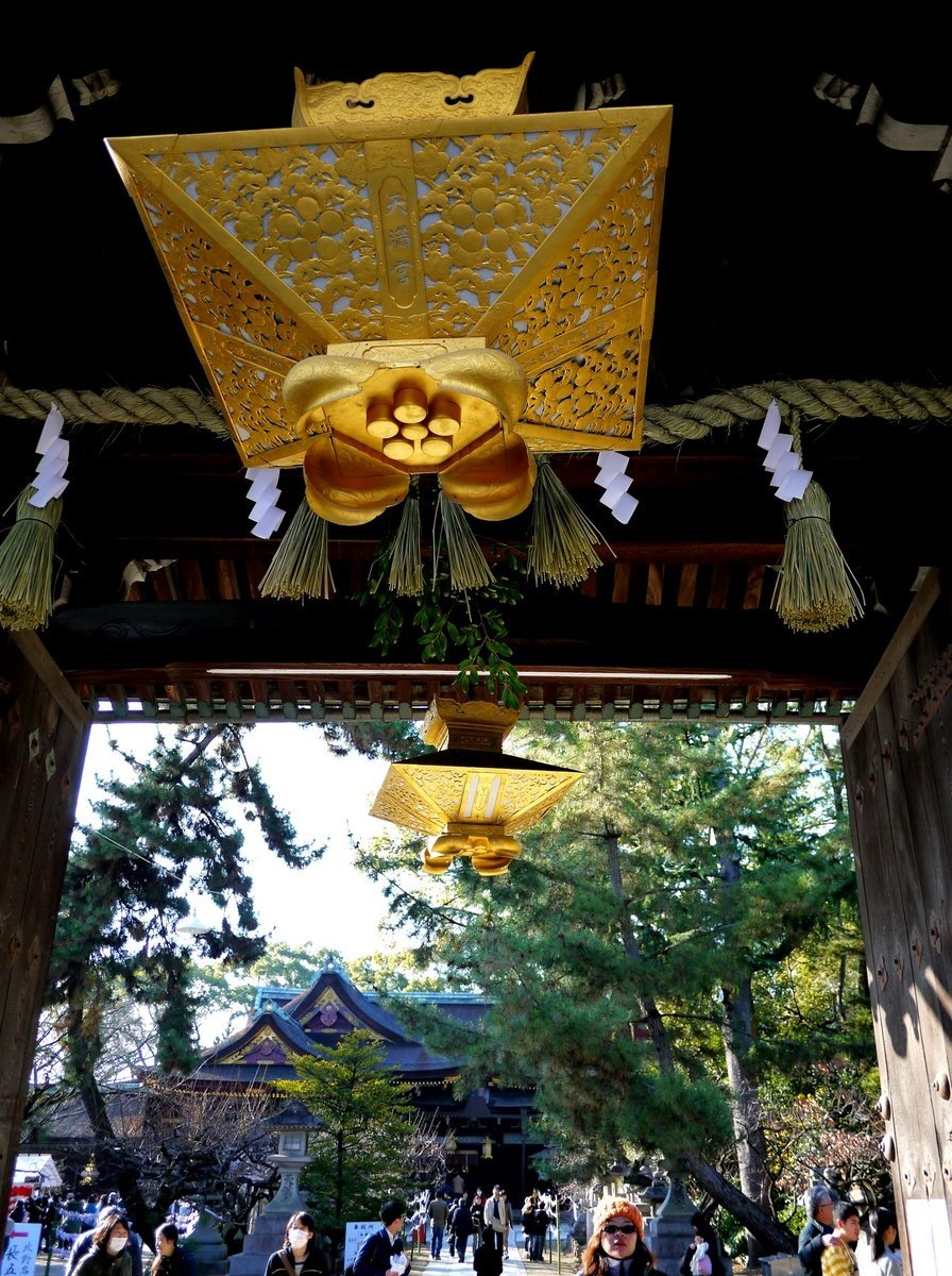 Ornate gold lanterns hang from the ceiling of the entrance gate