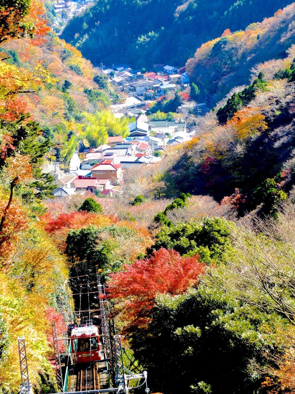 Глядя вниз с платформы станции на уходящий вниз фуникулер, гору и город